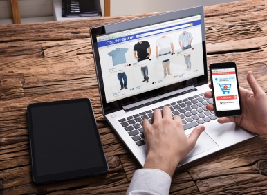 Businessperson Using Smartphone While Shopping Online On Laptop