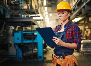 Concentrated young technician with clipboard in hands taking necessary notes