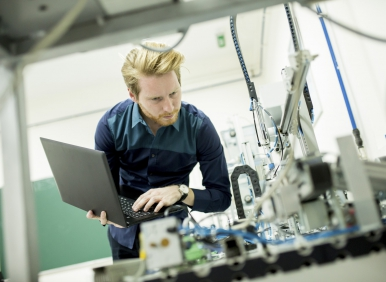 Engineer in the factory with laptop