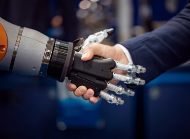 Hand Of A Businessman Shaking Hands With A Android Robot