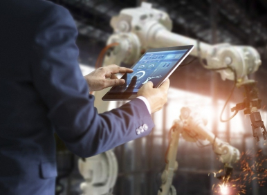 Industrial engineer manager using tablet control automation robot arms