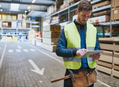 Young warehouse worker consulting a tablet