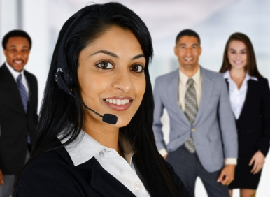 Five business dressed people facing the camera. The centre one wearing a headset