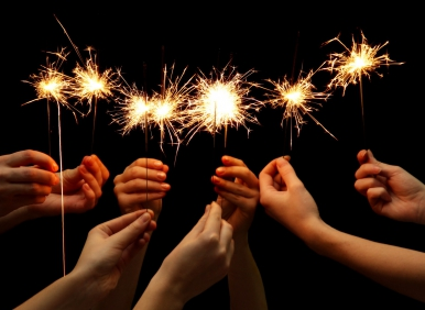 beautiful sparklers in hands on black background