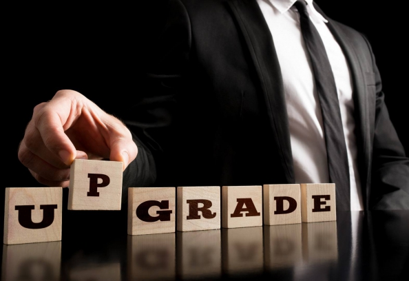 Upgrade Written On Wooden Blocks Being Picked Up By A Man In A Suit