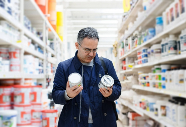 man choosing paint in hardware store