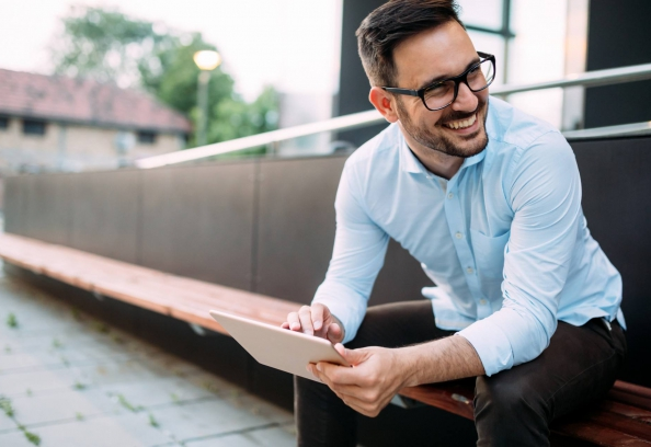 Businessman Sitting On Steps With Tablet Smiling