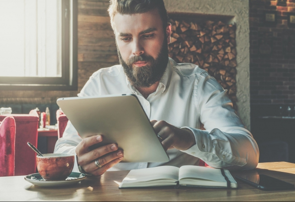 Young bearded businessman sits in cafe at table,uses digital tablet