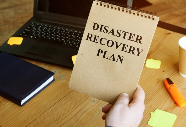 Disaster Recovery Plan written on a man's notepad