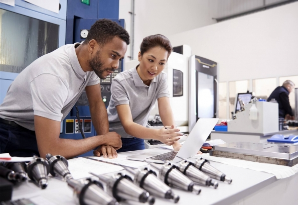 Man And Woman Looking At Computer In Factory